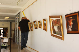 Workers set up for art exhibit.