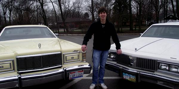 Michael DeBanto, a senior at Fairmont, poses with two of his collector cars