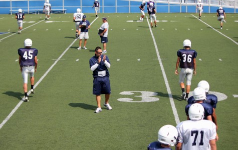 Fairmont's Varsity Football Coach  Andy Aracri shouts encouragement to the exercising team in the wake of the long-awaited Fairmont vs. Alter game on Friday, August 30th.