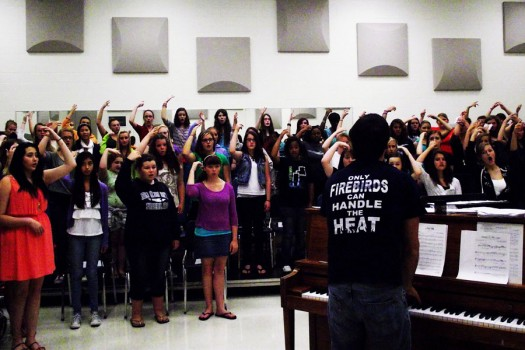 Choir students raise their hands to match their pitch.