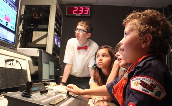 Fairmont Interactive Media students Harrison Webb, Becky Friedman and PJ Seabrook watch closely as Cub Scout Carter Almand mans the video switcher.
