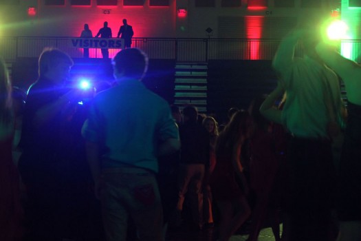 Three Fairmont staff members supervise student dancing at Homecoming from the safety of the track in Trent Arena. Their presence is often enough to keep students in line.