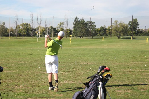 Senior Captian Jacob VanLeeuwen strikes the ball on Rolandia's driving range.