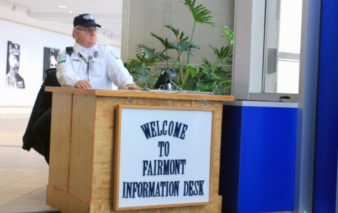 Security Guard David Fuchs sits at a desk by Fairmont's main doors and helps visitors who are coming into the school.