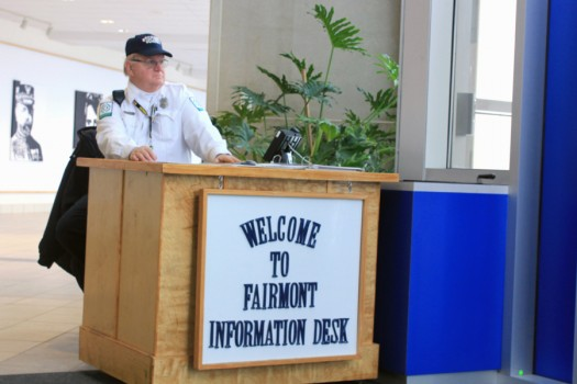 Security+Guard+David+Fuchs+sits+at+a+desk+by+Fairmont%27s+main+doors+and+helps+visitors+who+are+coming+into+the+school.
