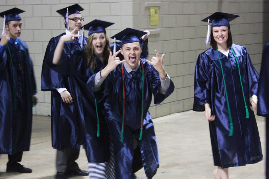 Senior Ryan Stacy gives the 'rock-on' gesture just before the ceremony begins. Behind him is Michelle Steinbrugge and at right is Hannah Spitler.