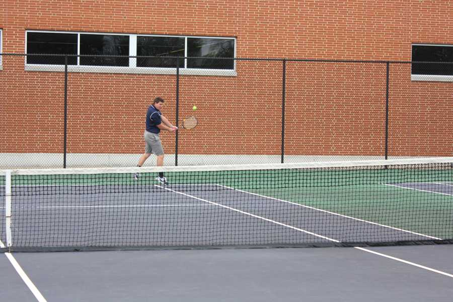 Sophomore Nate Powers works on his backhand before a match against Oakwood.