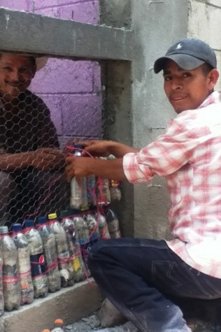 A local volunteer in Guatemala places eco-bricks in a building being constructed through the efforts of William Wynn's Liters of Learning program. The program was started by Fairmont grad Treva Wynn and her husband Riley Dowler.