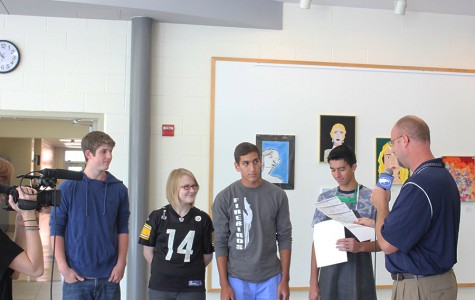 Principal Dan VonHandorf hands certificates to National  Merit Semifinalists Sam Barton, Sarah Kane and Jason Guadalupe and to National Hispanic Scholars Jason Guadalupe and Alex Heindl. An Interactive Media student films the event.