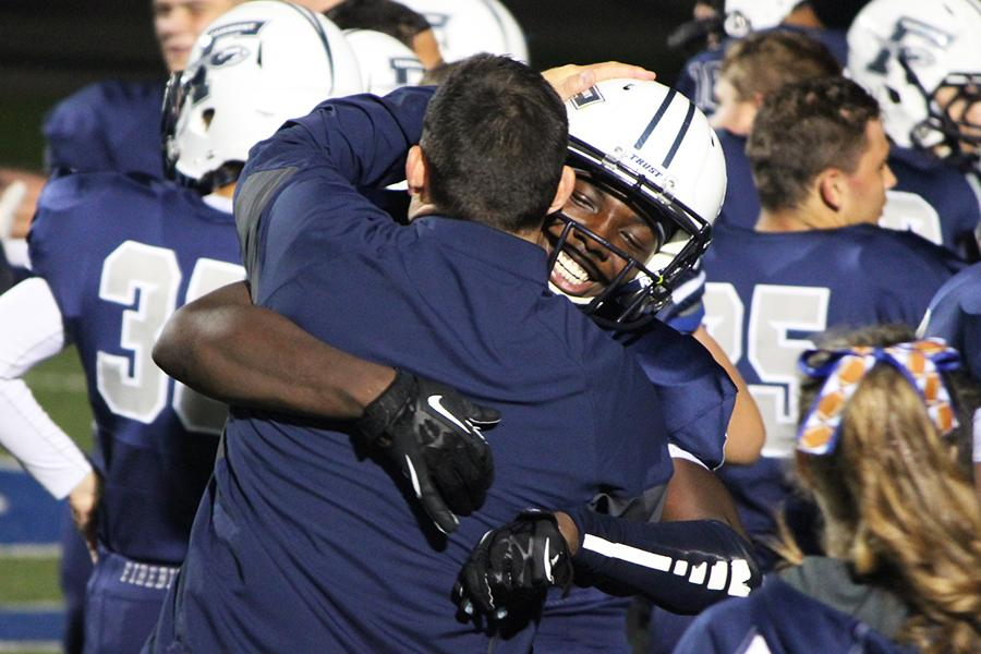 Head Coach Andrew Aracri and senior wide receiver Kei'Vante Tanner embrace after his dominating performance in the Firebirds' victory over St. John's (Toledo). Tanner had 3 receptions for 137 yards and 2 touchdowns.
