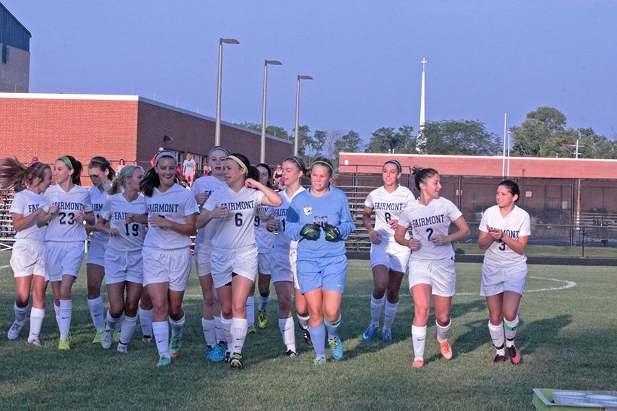 The+Varsity+girls+soccer+team+runs+in+for+a+team+huddle+before+the+beginning+of+their+match+against+Troy.+%28Photo%3A+Lindsay+Breslin%29