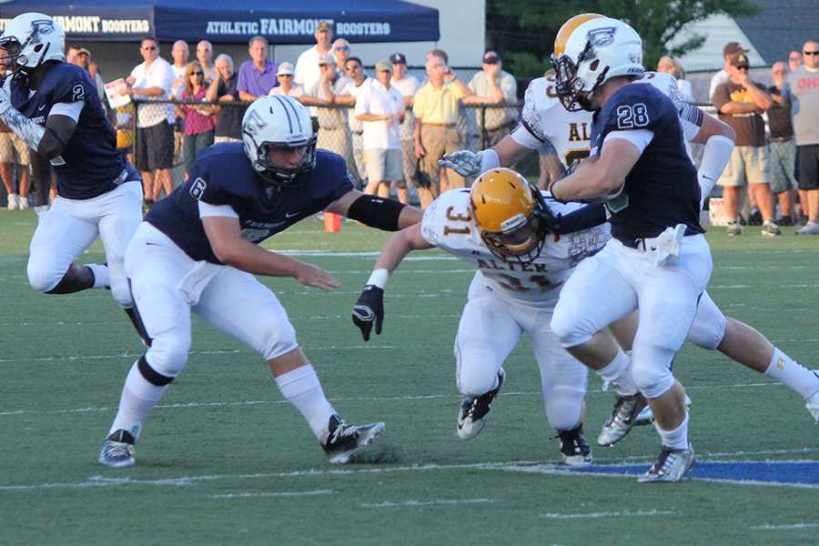 Fairmont sophomore, Nick Moreland, stiff arms number 31 from Alter.