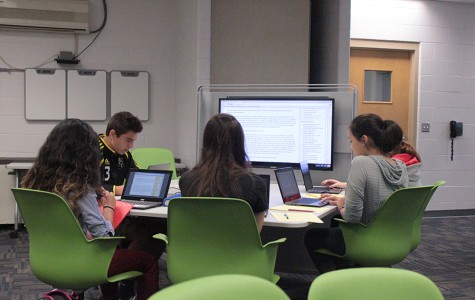 A small group of freshmen English students collaborate on a project in the 21st Century Classroom. Fairmont plans to make some of this  classroom's technology available in the library and the FIC.