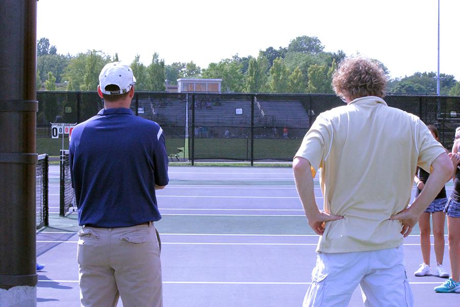 Head coach Matthew Hughes stands his ground on Fairmont's home tennis court as the the Alter coach stands beside him. (Photo: Lindsay Breslin)