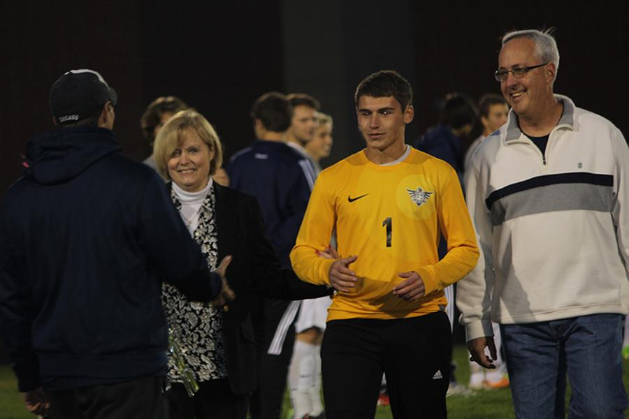 Jackson Havener walks with his parents on senior night and shakes the hand of his coach.