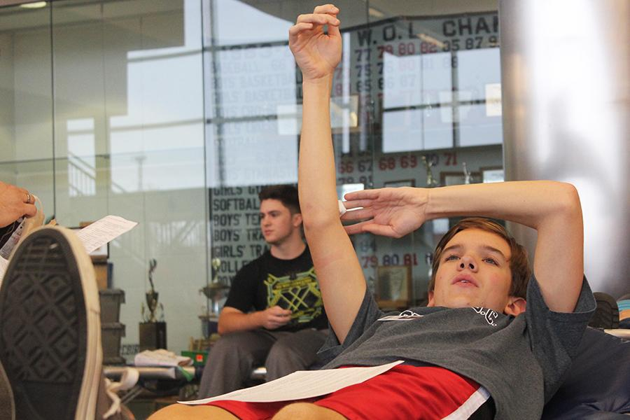 Luke raises his hand after giving blood in order to stop the bleeding from the needle point.