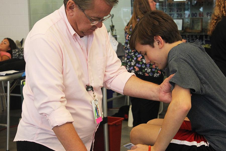 Luke is helped up by one of the volunteers after giving blood.
