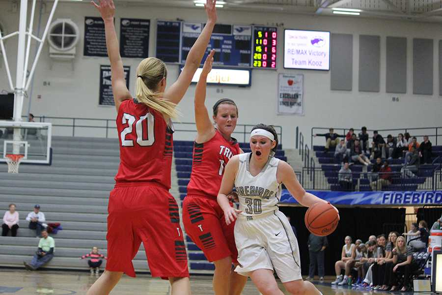 Junior Celeste Etter drives through two Troy defenders for a layup.