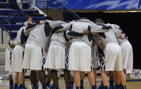 Fairmont's Varsity Boys' Basketball Team huddles before their game against Graham High School. The boys are having a great season, with a record of 14-2.