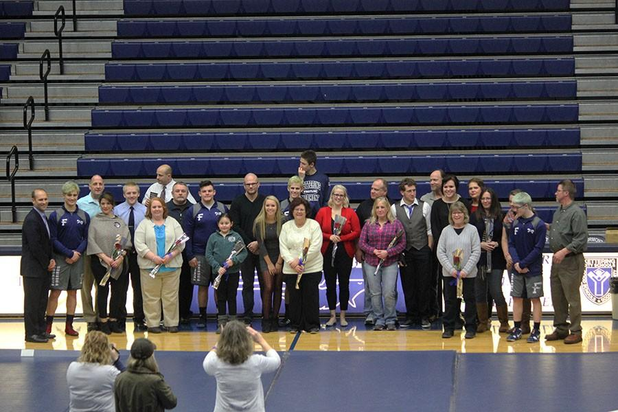 All of the senior parents line up with their student to pose for a picture.