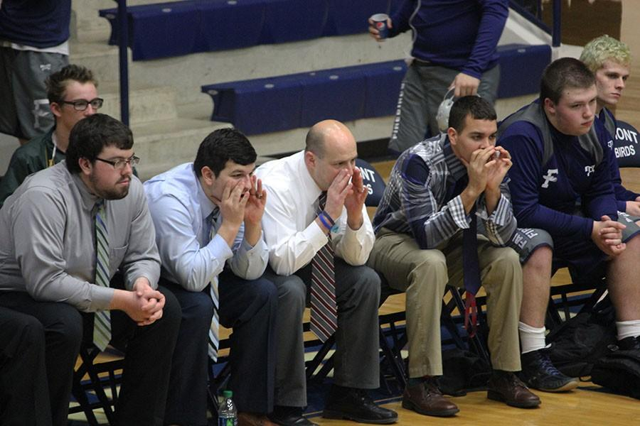 Coaches yell encouragements to the wrestlers.