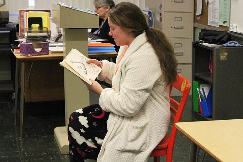 Senior Caitlyn Black reads a childrens story to her English class, taught by Julie Wallner.