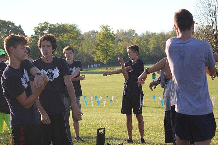 The boys' cross country team stretches in preparation for the race.