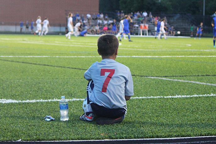 Metro parks soccer player watches the varsity game from the sidelines.