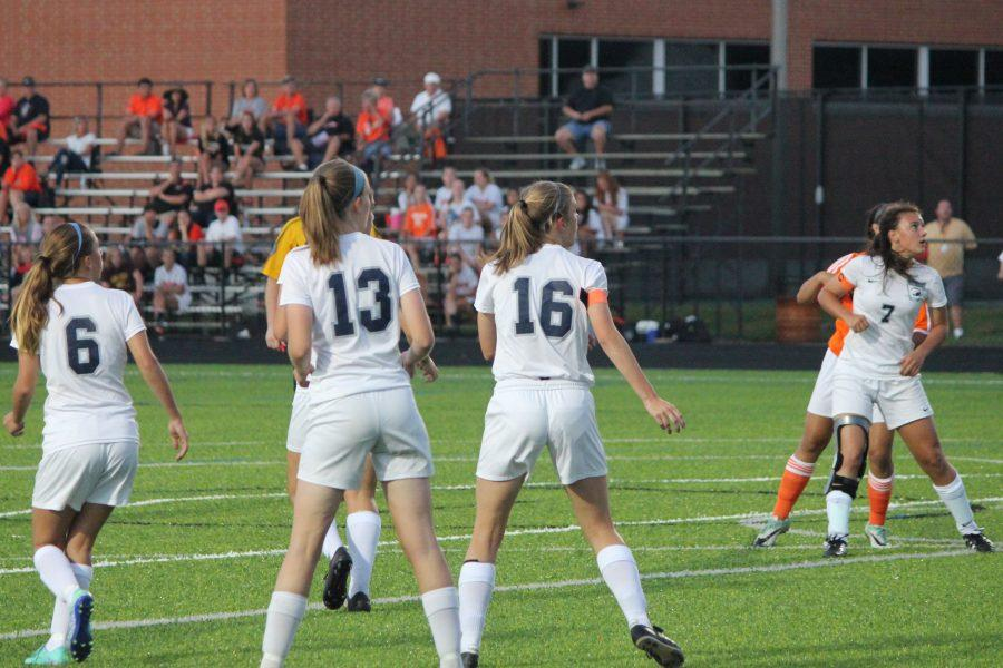 The varsity players are attentive to the play that is happening on the field.