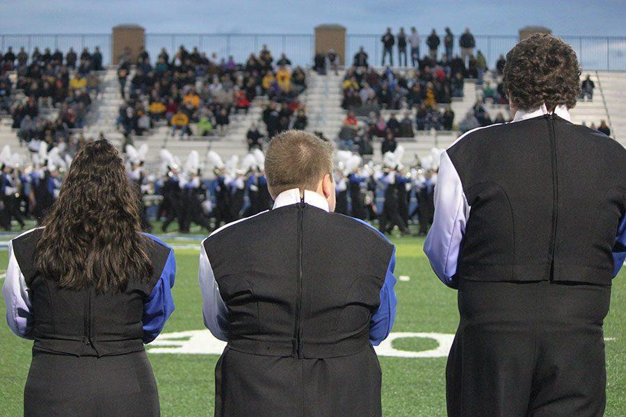 Fairmont marching band seniors look upon fellow members as they march on Roush for the last time