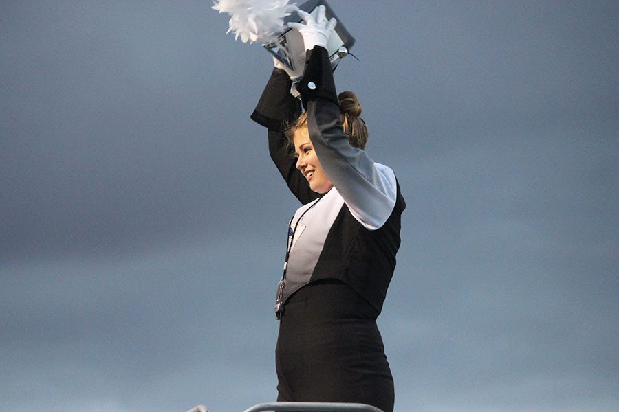 Senior Sidney Oliver  lifts her hat as she conducts Fairmont marching band