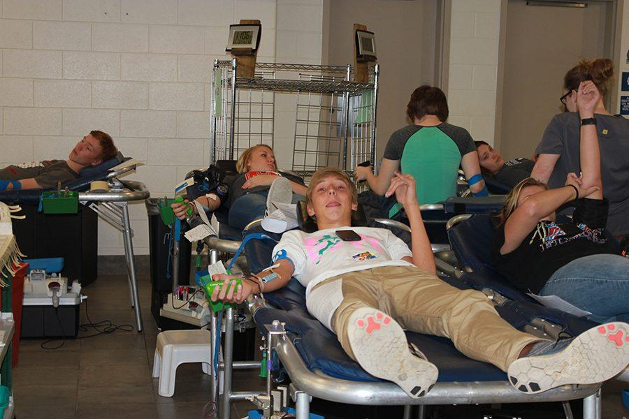 Sophomore Andrew Sarmir posing for the camera while donating blood.