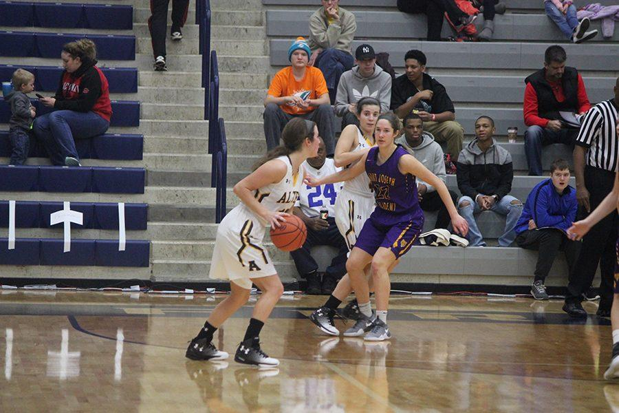 A player for Alter is attempting to throw the ball to a fellow teammate, but the teammate is being guarded by number twenty-two for Saint Joseph.