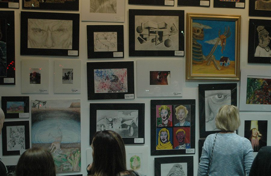 People from the community admire the works of art.