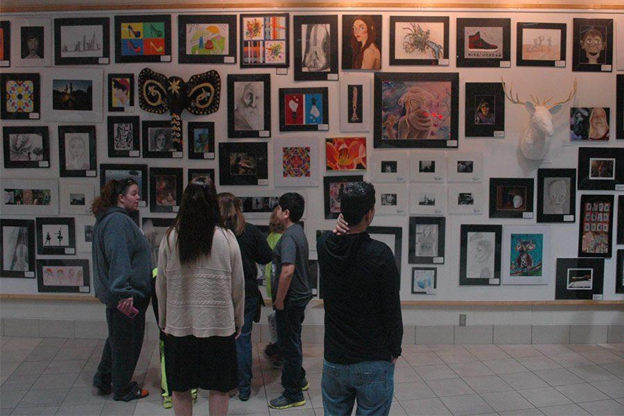 Parents and students gaze at the abundance of artworks.