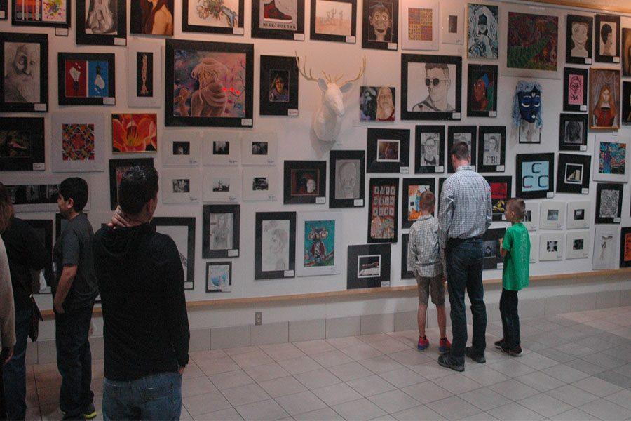 A Kettering family admires the artwork of the students.