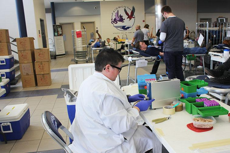 A lab technician works on the blood.