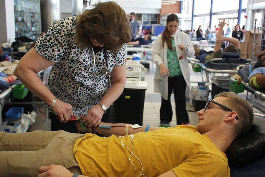 Junior, Nathaniel Harm, watches as a nurse finishes taking his blood.