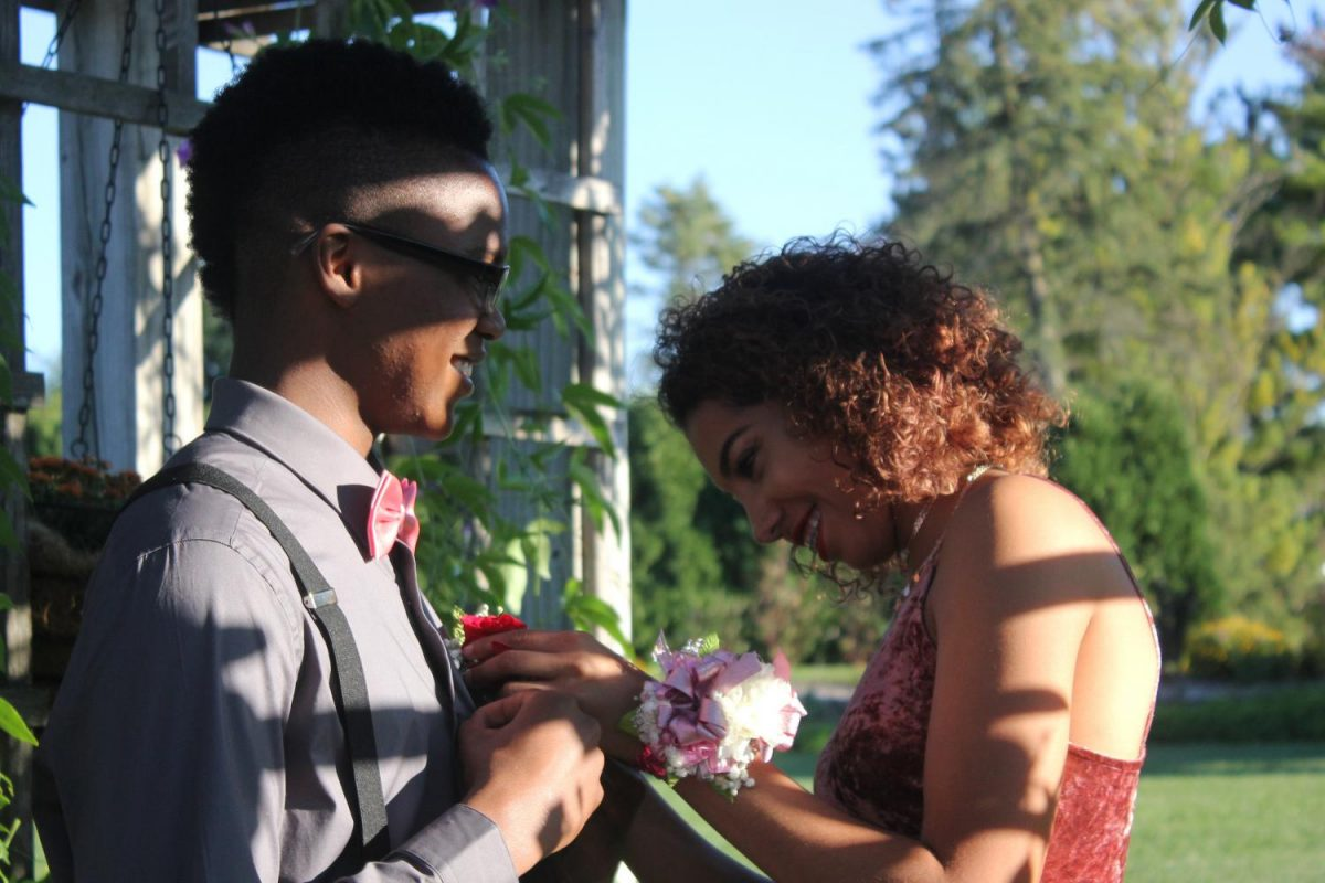 Sophomore%2C+Kayla+Morris+has+a+laughing+moment+with+sophomore%2C+Jairi+Walker+while+pinning+his+boutonniere.