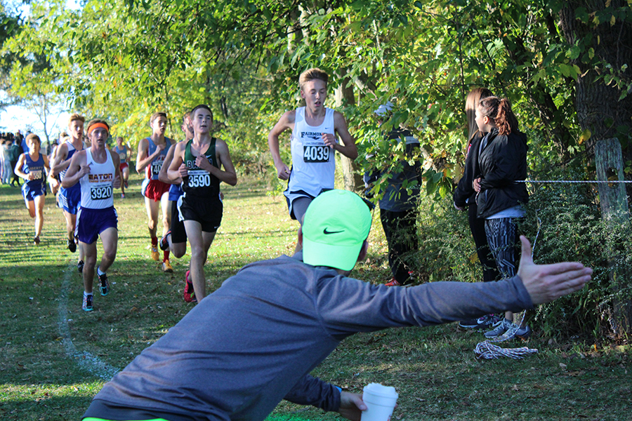 Coach Aaron Baker directs Andrew Sarmir around the turn of the course.