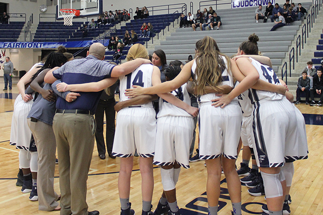 The Girls Basketball team come together before the start of the game to discuss game plan.