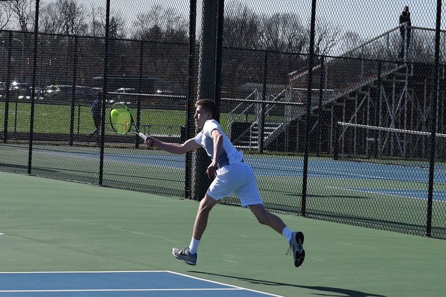 Senior, Ethan Webb attacks the ball with the racket.