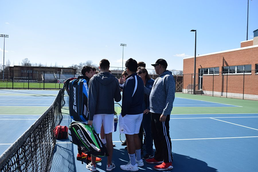 The boys varsity tennis team gathers up before the match.