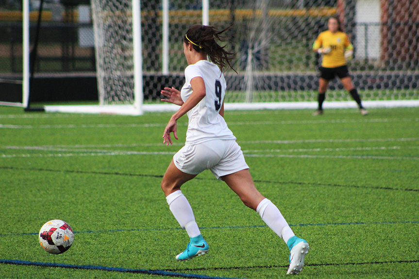 Senior, Maddie Seaman making her way down the field to attempt to score a goal.