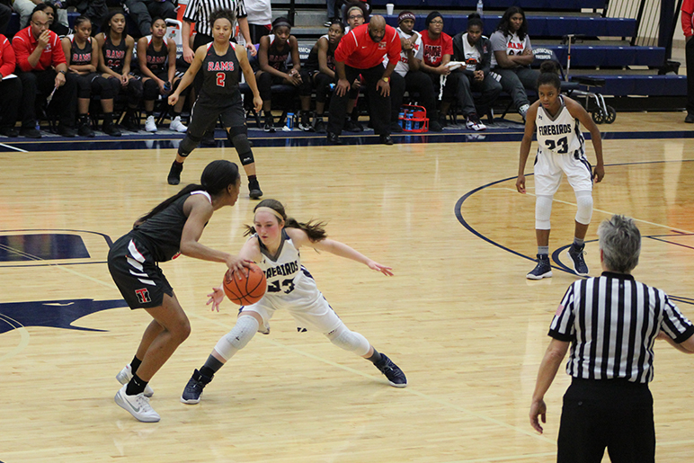 Sophomore, Ashley Daniels attempting to steal the ball while playing defense against the Rams.