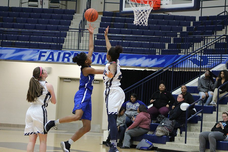 Junior, Makira Webster going up high to attempt to block her Xenia opponent.