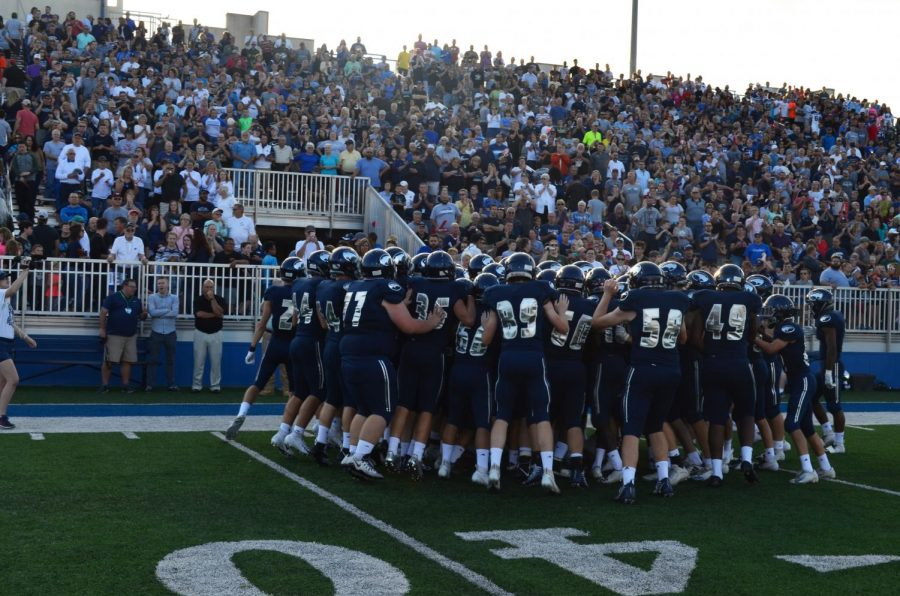 Members of the football team huddle up after running onto the field to a roaring home crowd. The Birds are set to take the field for kickoff.