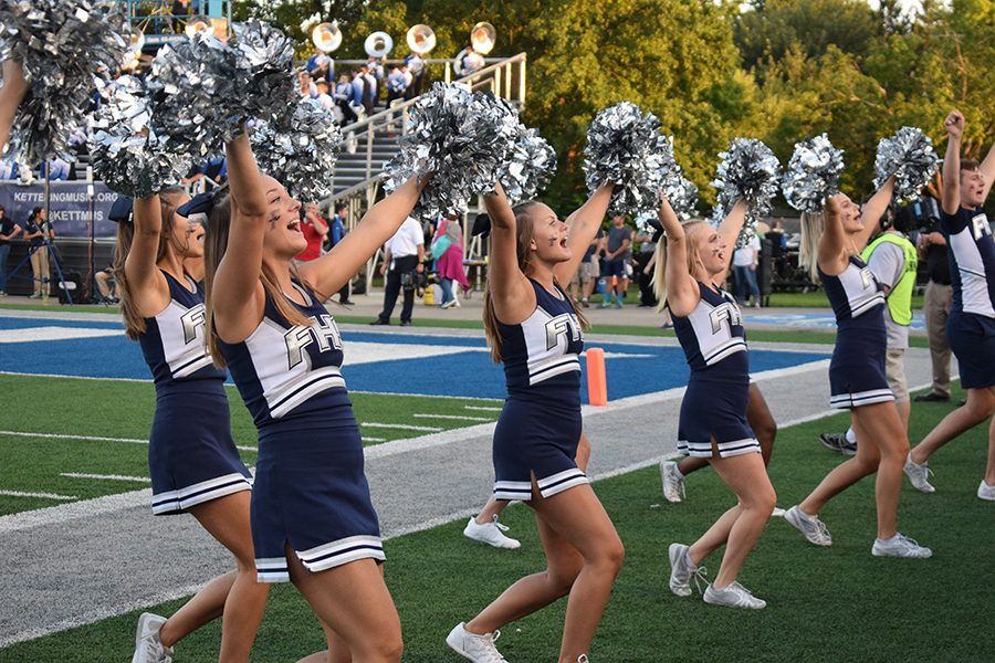 Varsity cheerleaders pump up the Loud Crowd during the first half. The varsity football cheerleaders are known for their tradition of cheers and dances during football games.