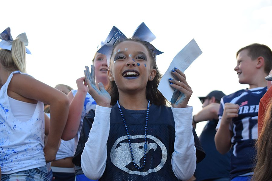 A Peewee Firebird Cheerleader enjoys the halftime show put on by the Fairmont Marching Firebirds and Color Guard.