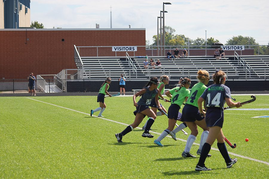 Junior Stella Fiscus and senior Dominique Fero run to get the ball away from Oakwood. The teamwork was successful in getting towards the goal.